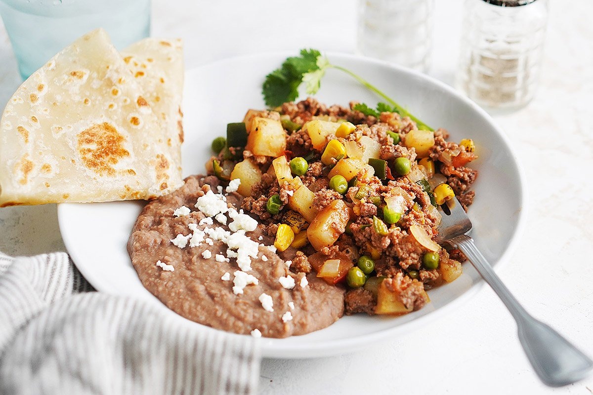 A white plate with ground beef and beans and a tortilla on the side