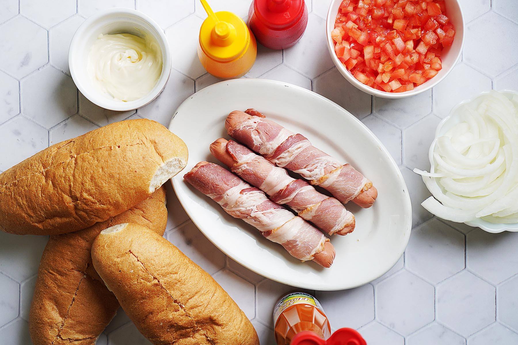 Hot Dogs ingredients on a board: buns, dogs wrapped in bacon, sliced onions, chopped tomatoes, mayo and mustard.