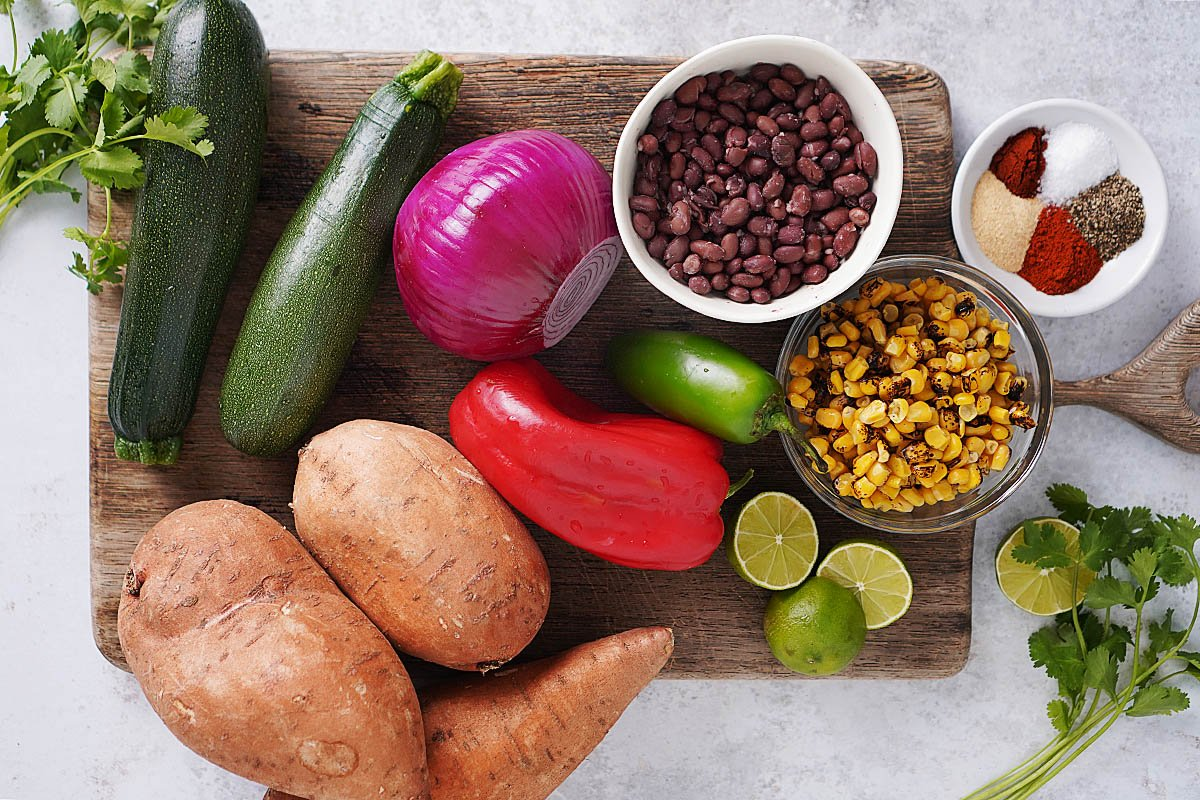 Ingredients on a cutting board: whole zucchinis, red onion, sweet potatoes, red bell pepper, jalapeño, black beans, corn kernels, spices