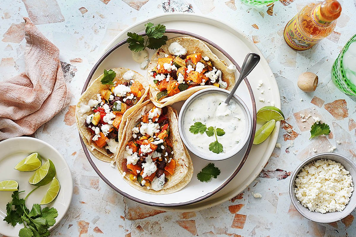 3 tacos on a plate with crema on the side in a little bowl