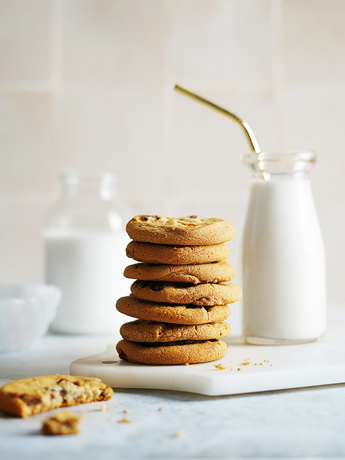 A stack of Chocolate Chip Cookies and a glass of milk on the side.