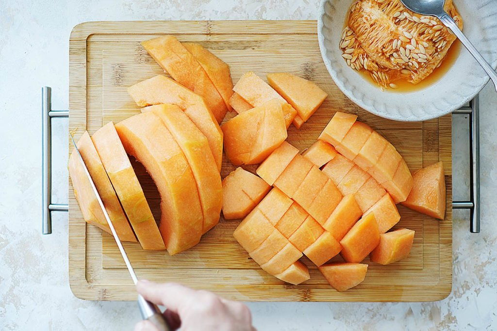 Cutting watermelon chunks on a cutting board.