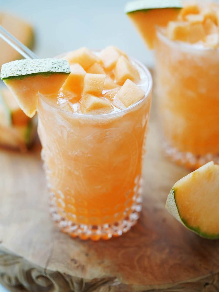 A glass with melon water and chunks on top of the glass.
