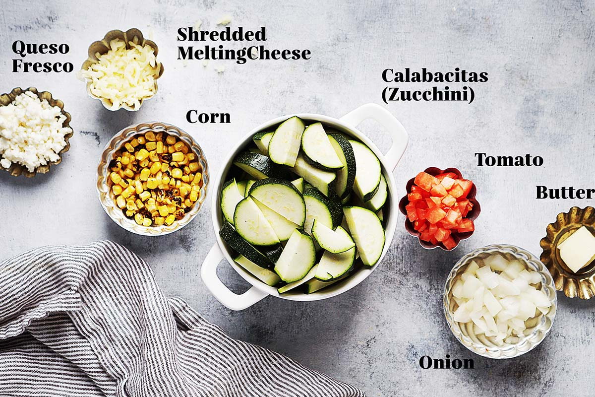 Ingredients on small bowls: queso fresco, shredded cheese, corn, zucchinis, tomato, onion and butter.