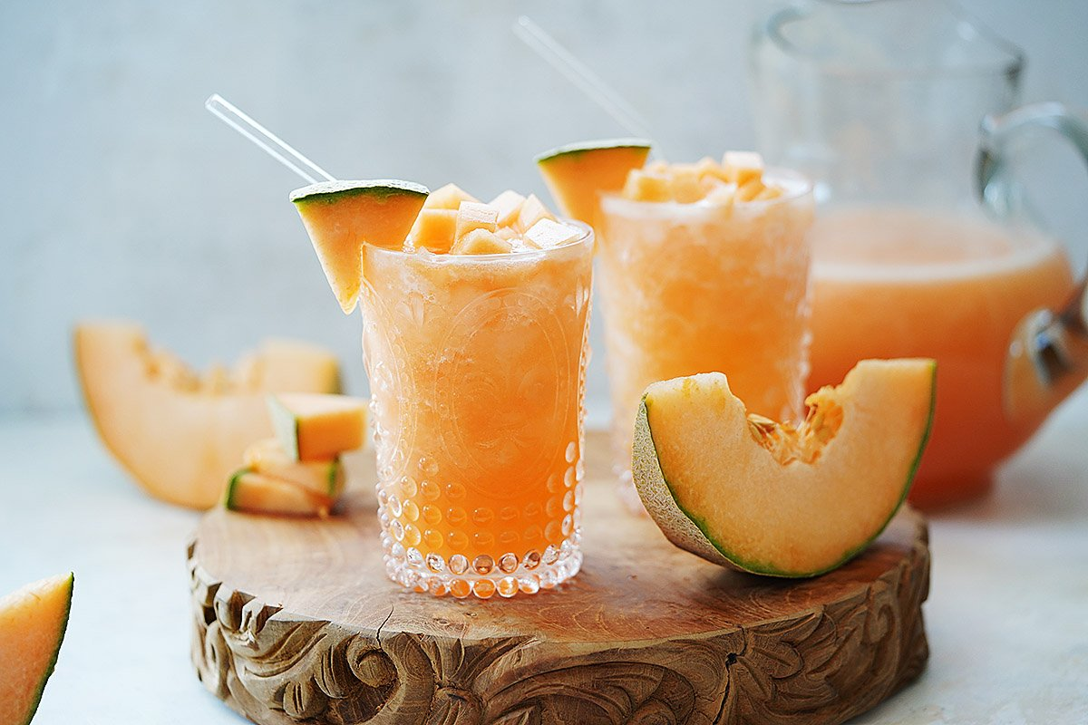 Agua De Melon in two glasses and cantaloupe slices on the side.