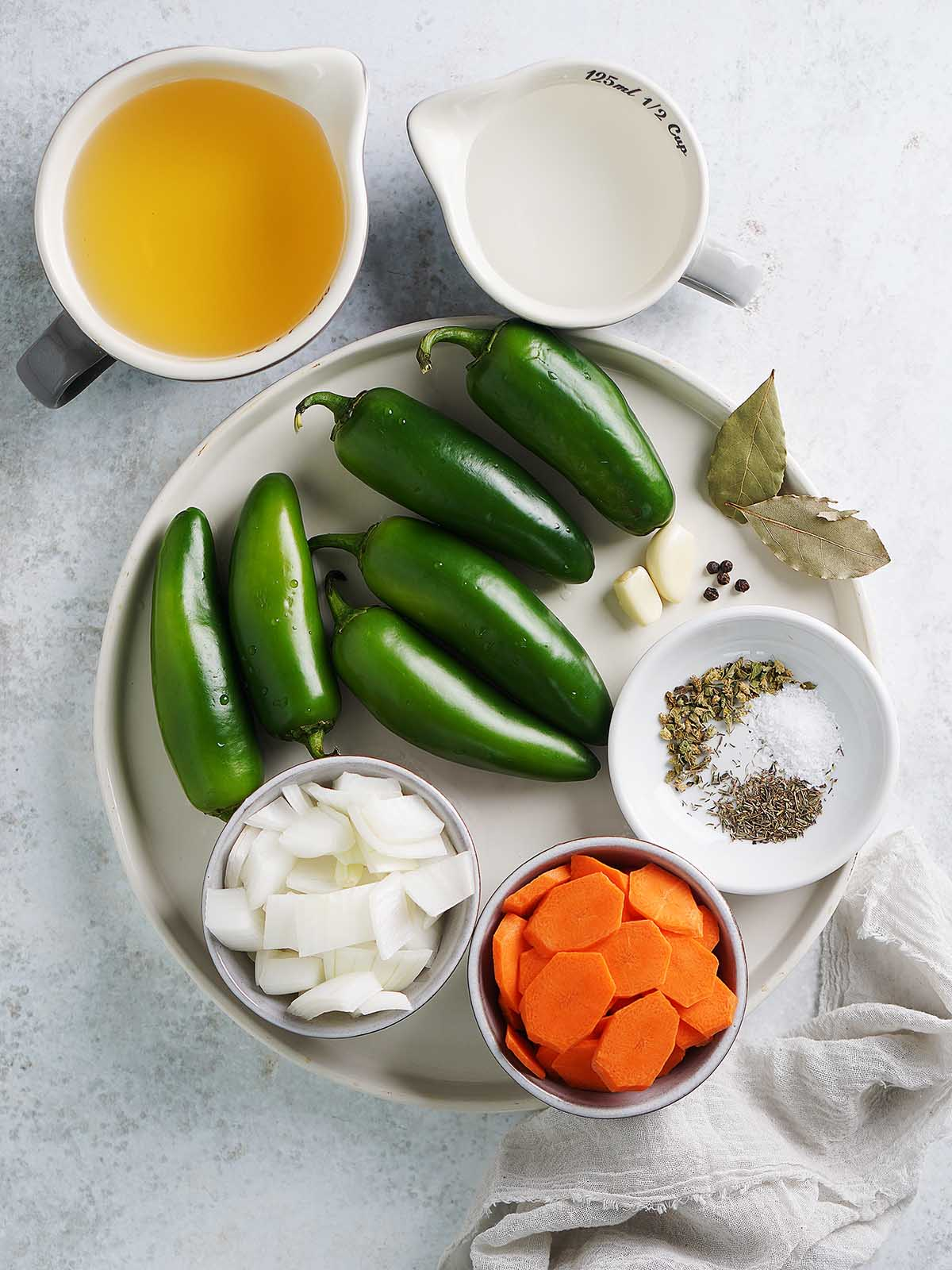 Ingredients on a white plate: jalapeños, sliced carrots, sliced onions, spices and herbs.