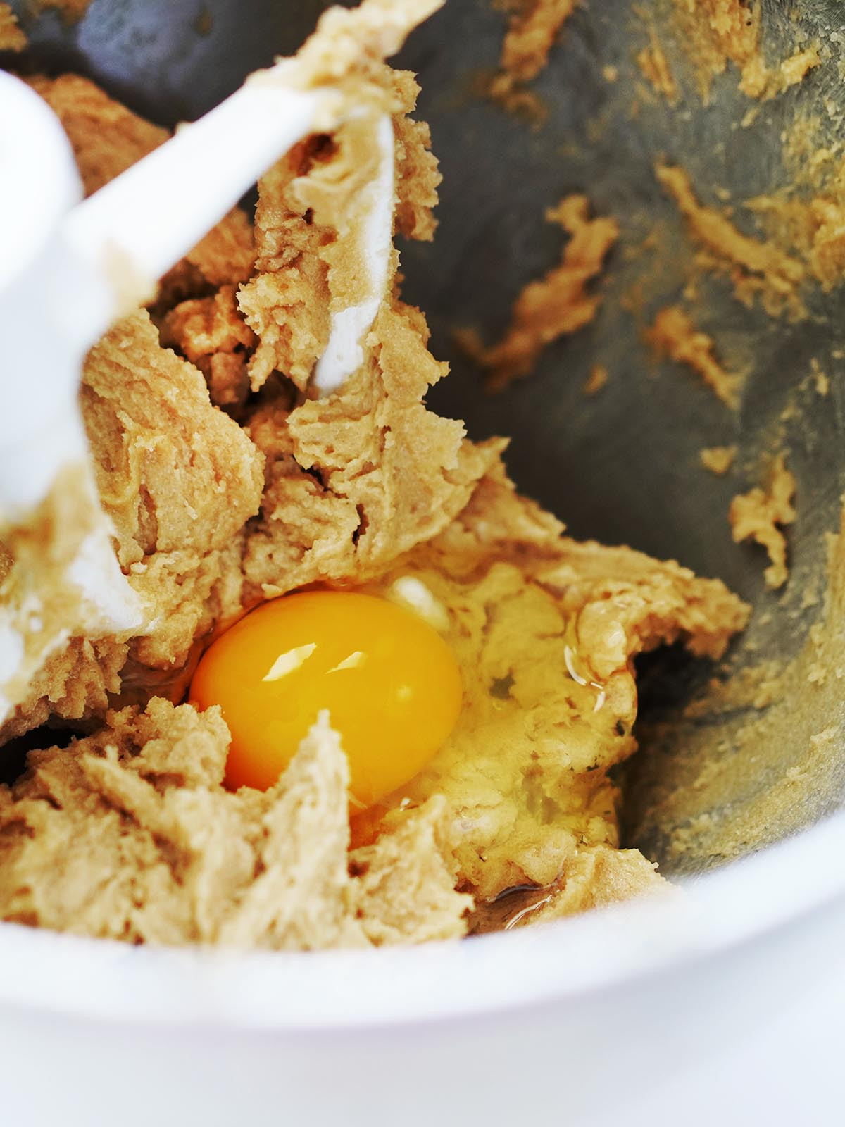 An egg on top of cookie dough inside a mixer.