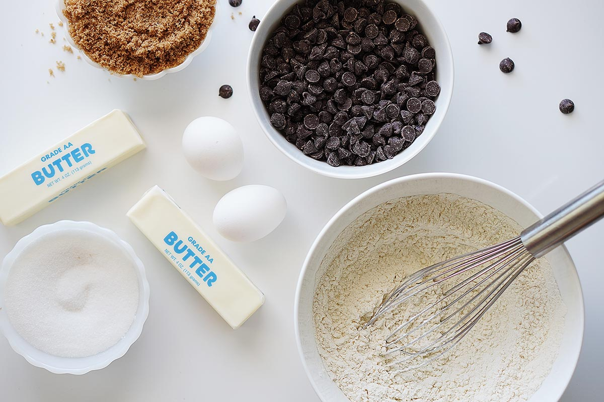 Ingredients on a white table: brown sugar, butter, white sugar, flower, 2 eggs and chocolate chips.