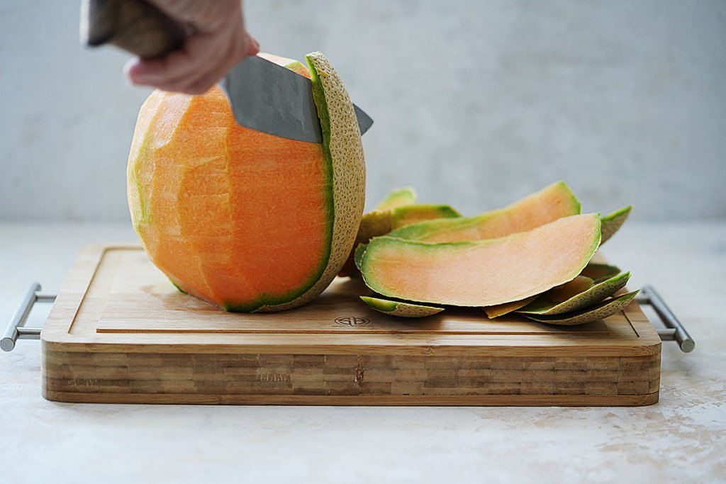Removing cantaloupe's skin with a knife.