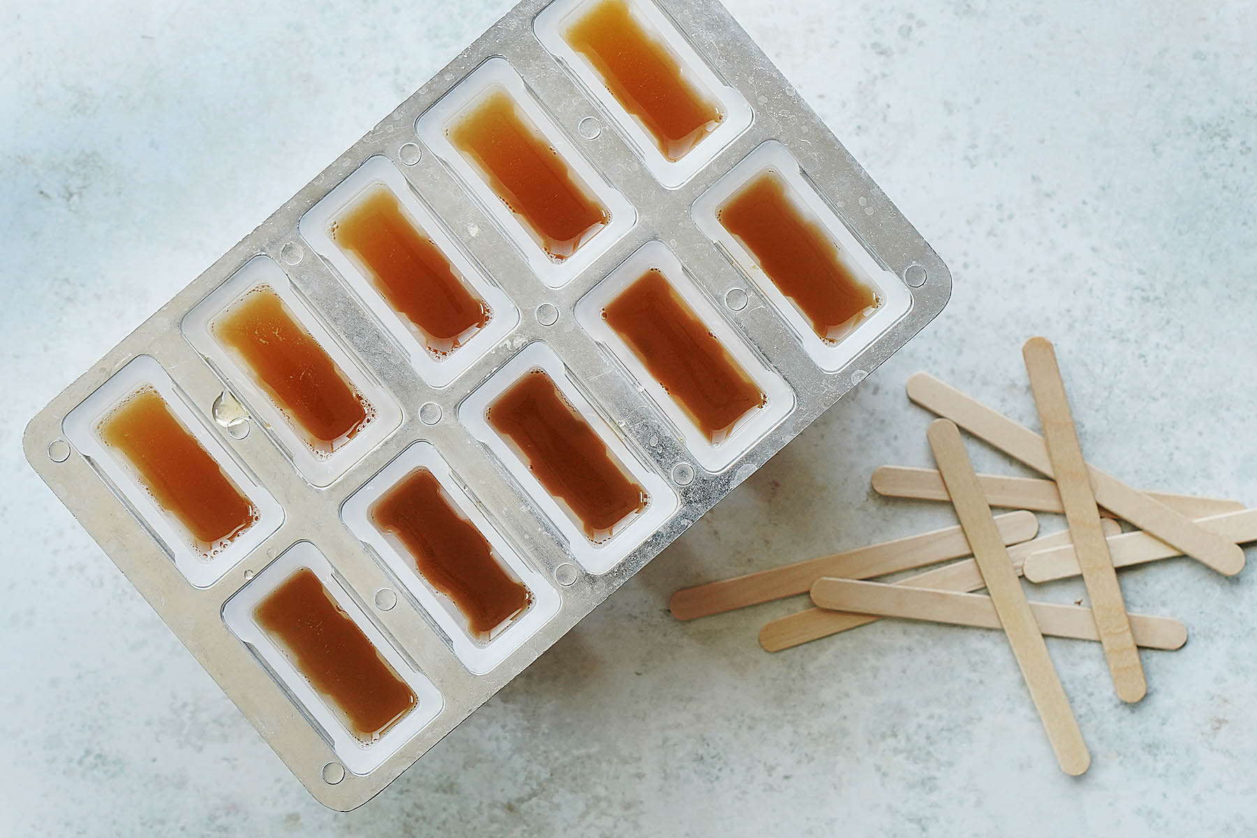 Popsicle molds with juice in them and popsicle sticks on the side.