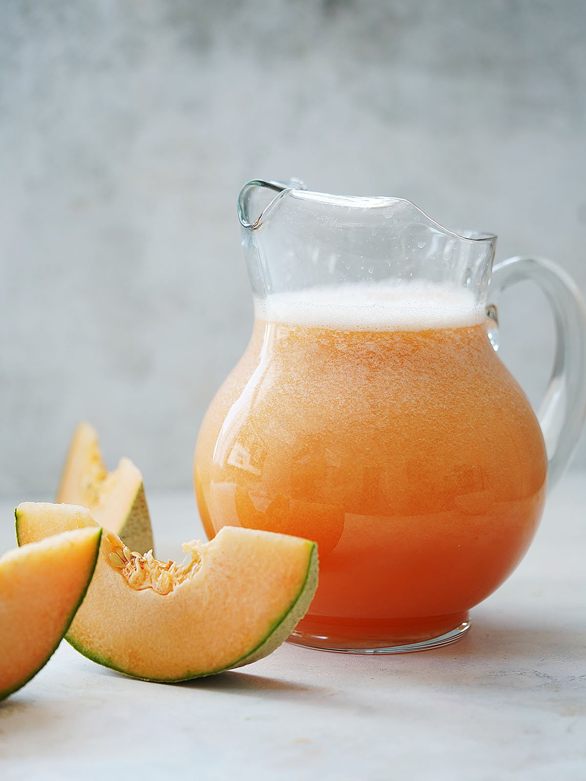 A jar with cantaloupe water and cantaloupe slices on the side.