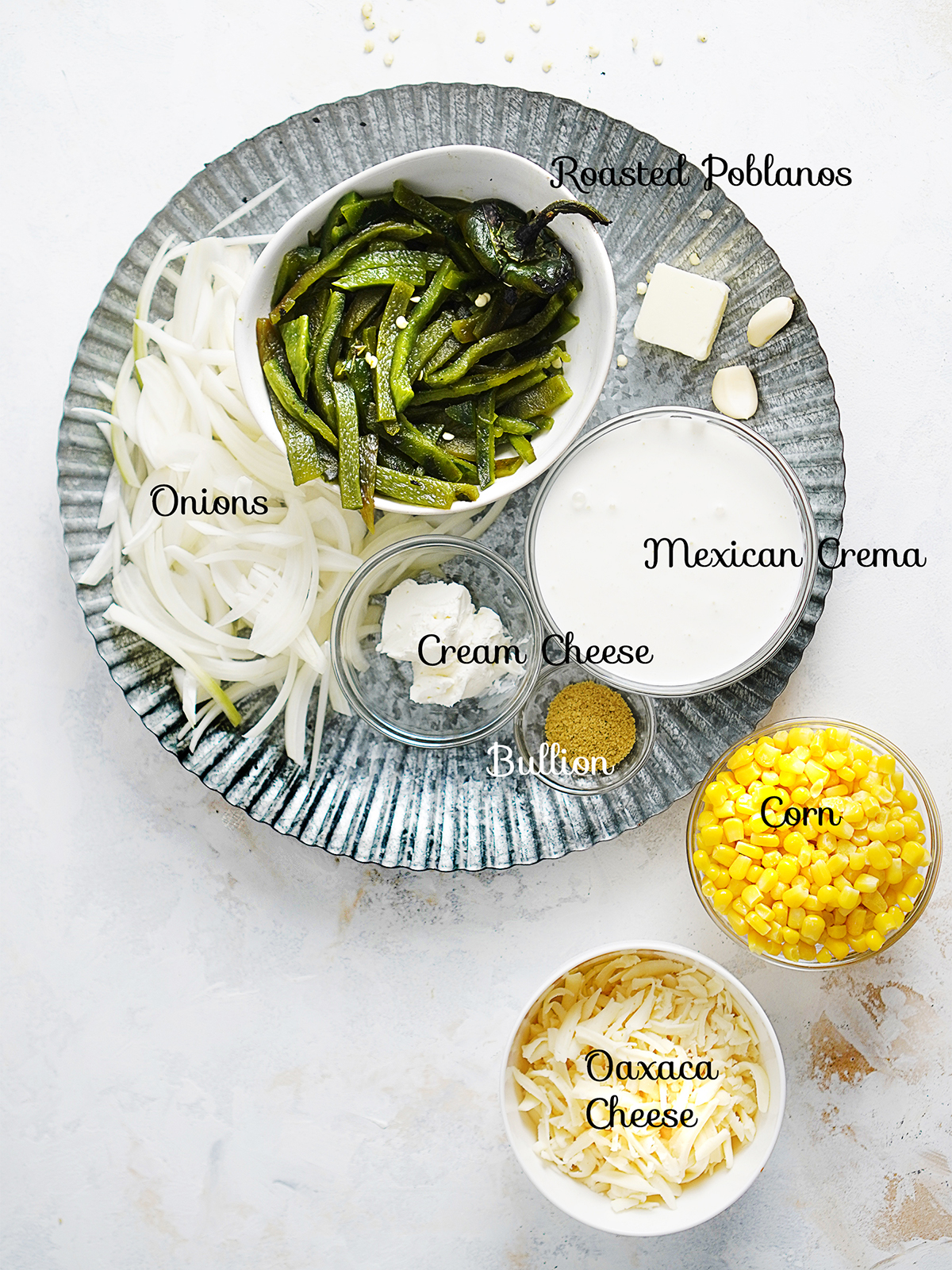 """Ingredients on a plate placed in small bowls"""" corn, shredded cheese, roasted poblano peppers, cream cheese, mexican crema, onions, and bullion powder."""