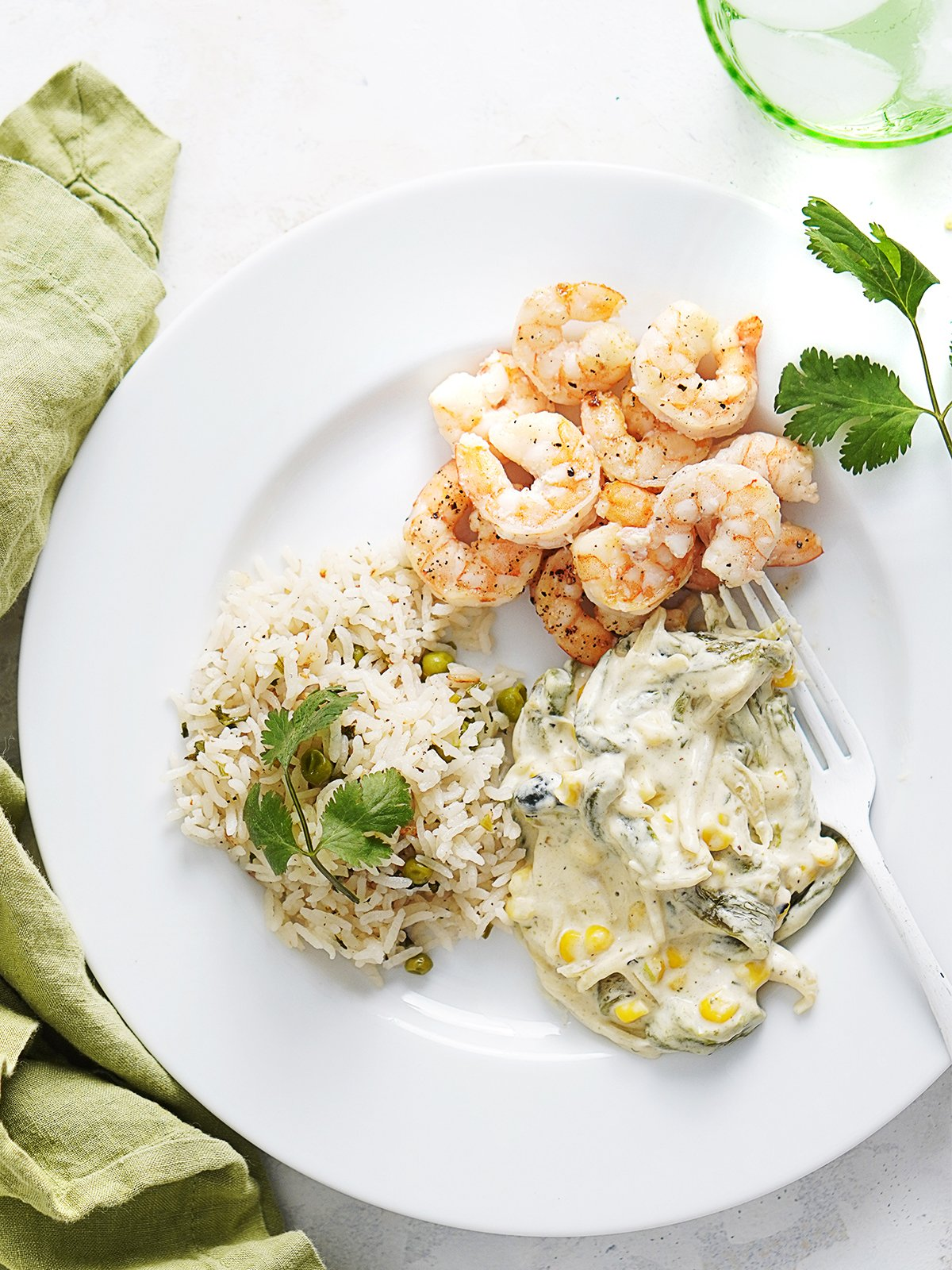 A white plate with rajas, rice and shrimp with a green napkin on the side.