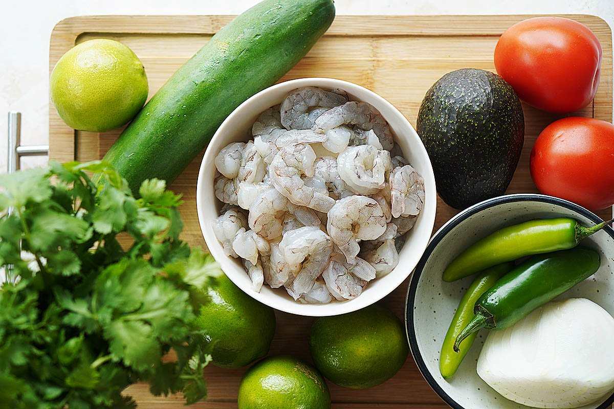 Ingredients on a cutting board: peeled shrimp, cucumber, tomatoes, avocado, jalapeños, onion, limes and cilantro.