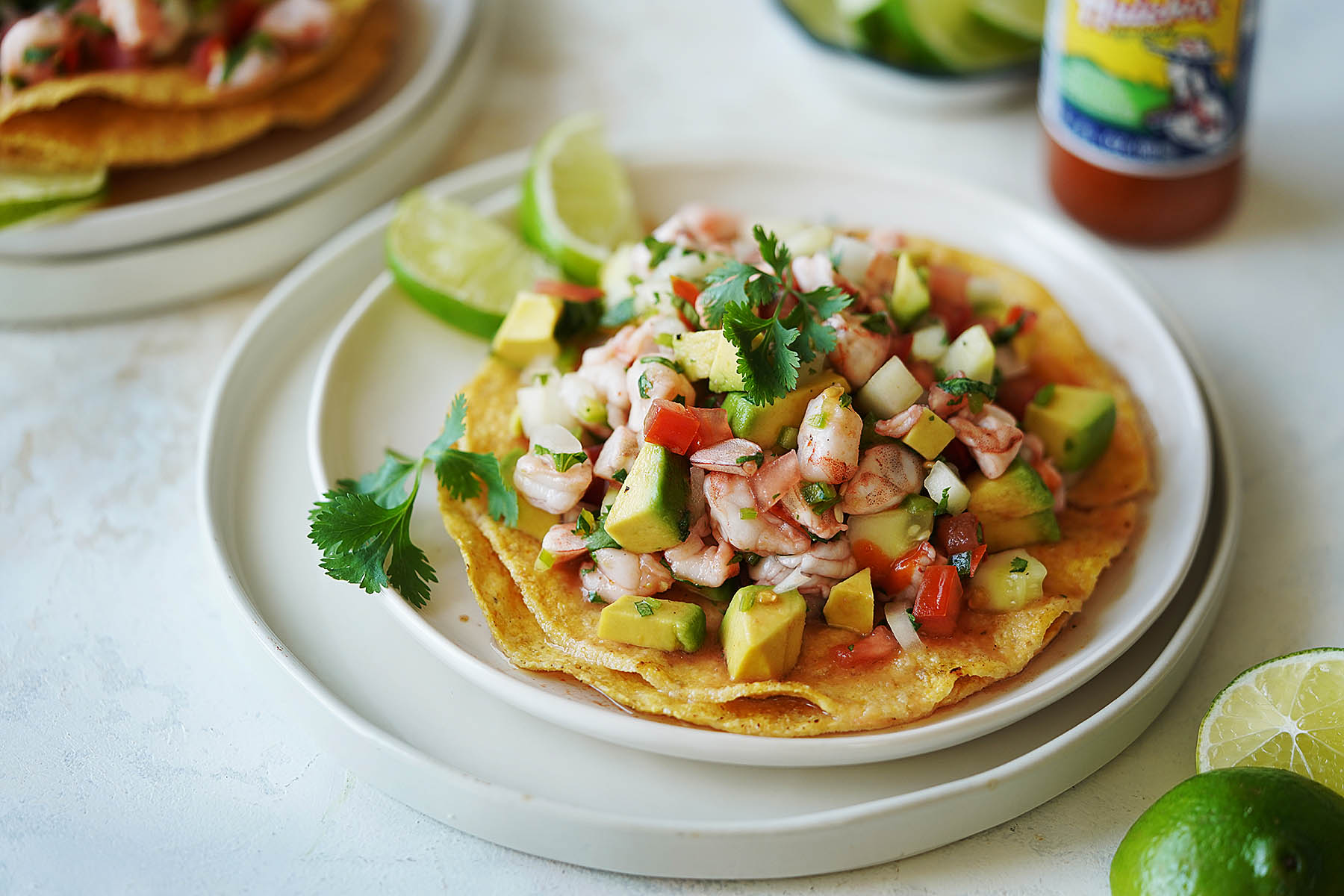 A shrimp ceviche tostada on a white plate and limes on the side.