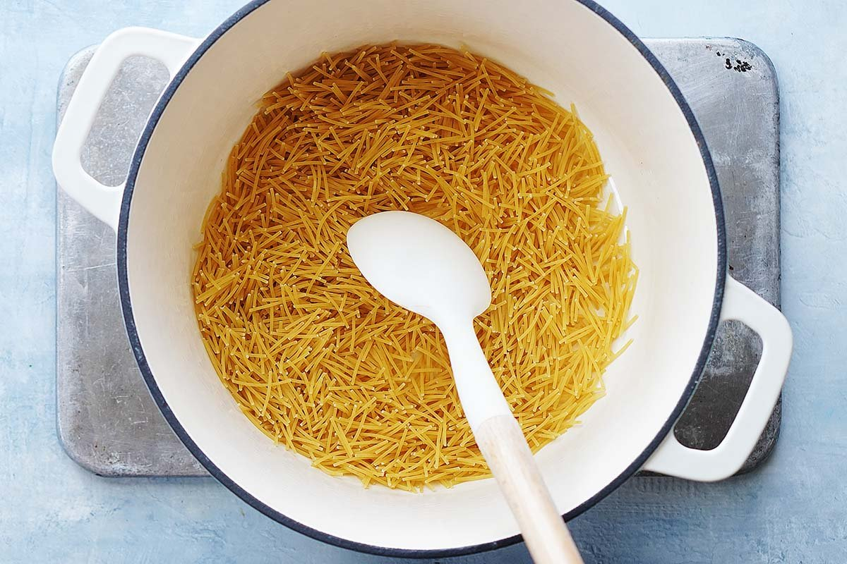 Fideo pasta in a white pot and a white spoon.