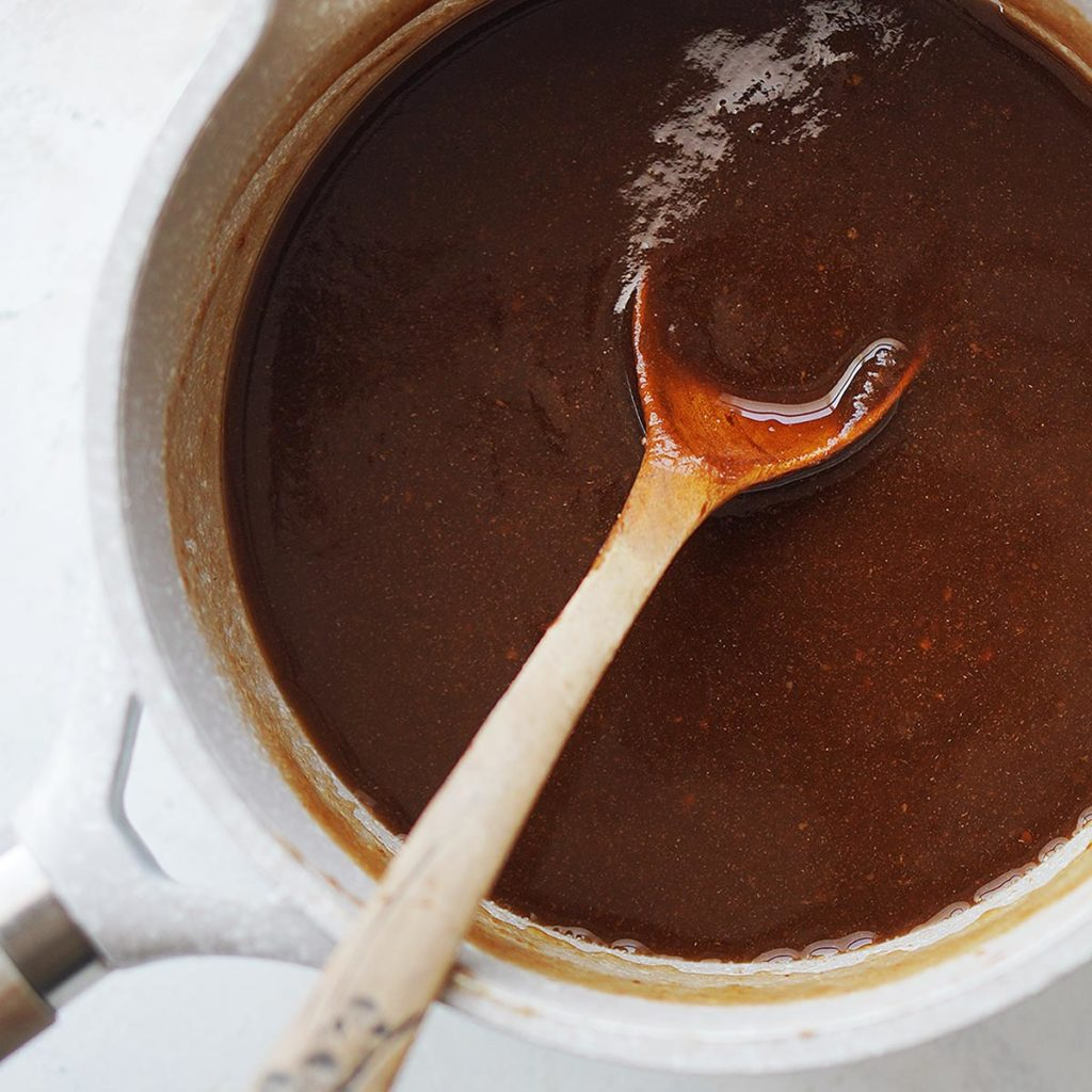 A small sauce pan with the paste and a wooden spoon.