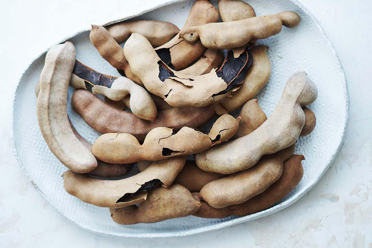 Tamarindo pods on a white plate.