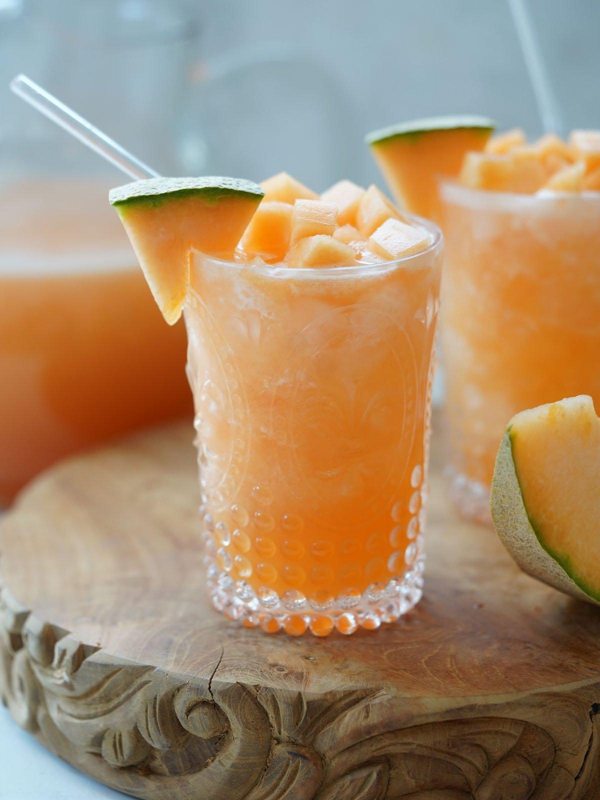 A glass with agua de melon topped with cantaloupe chunks.