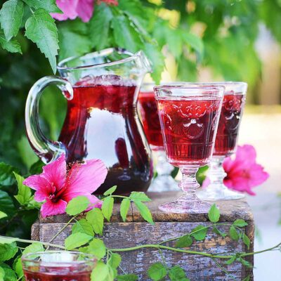 A jar and 3 glasses with a red drink in an outdoor setting.