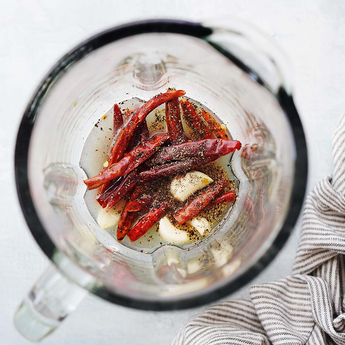 Chile de arbol peppers, garlic and lime juice inside the glass of a blender.