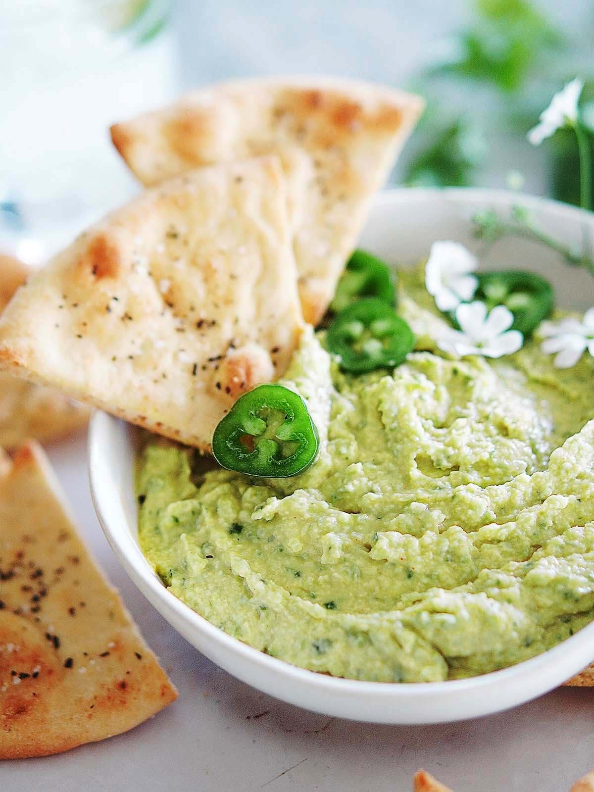 A bowl with Cilantro Jalapeño Hummus and chips on the side.