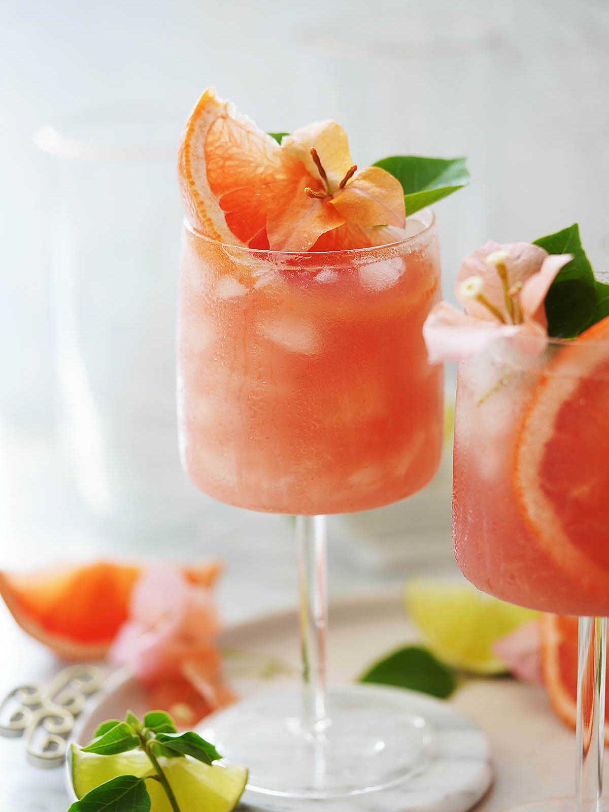 Paloma cocktail garnished with grapefruit and an orange flower.