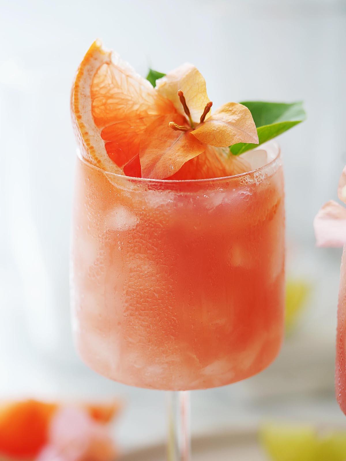 An orange drink garnished with grapefruit and an orange flower.
