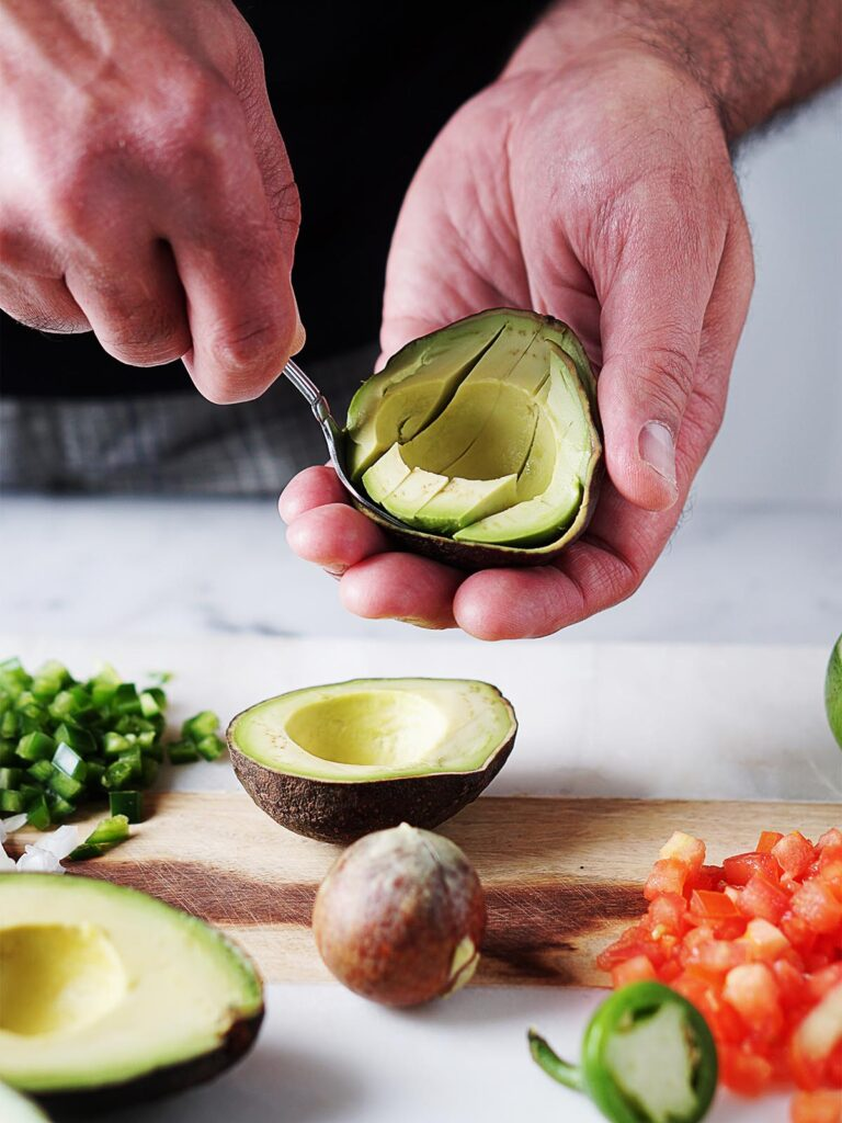 Two hands cutting an avocado.