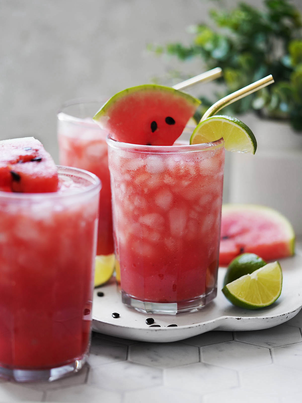 Three glasses with agua de sandia and limes on the side.