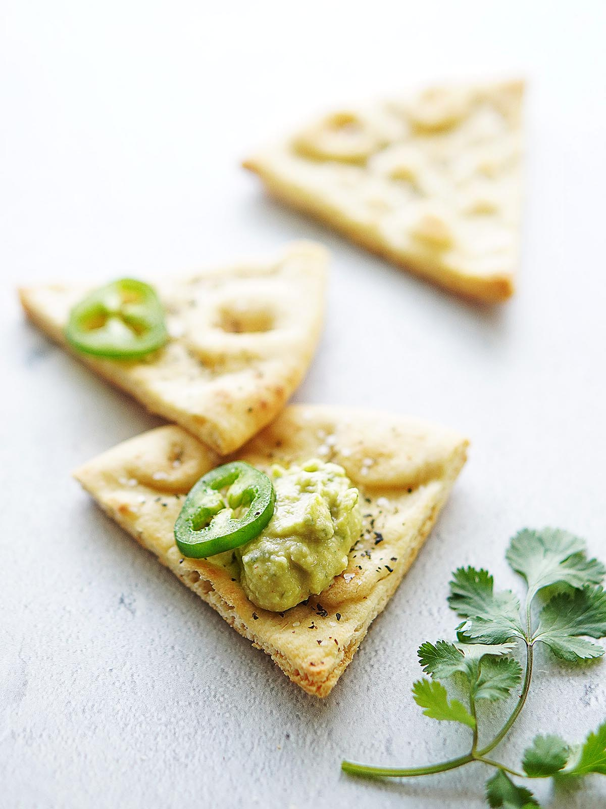Crispy pita chips on a blue table with cilantro on the side.