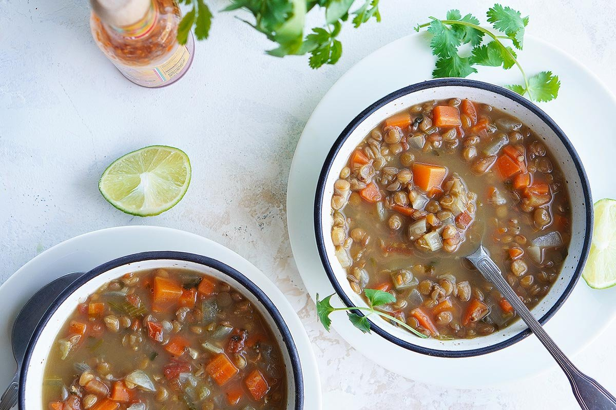Two bowls of soup with limes on the side.
