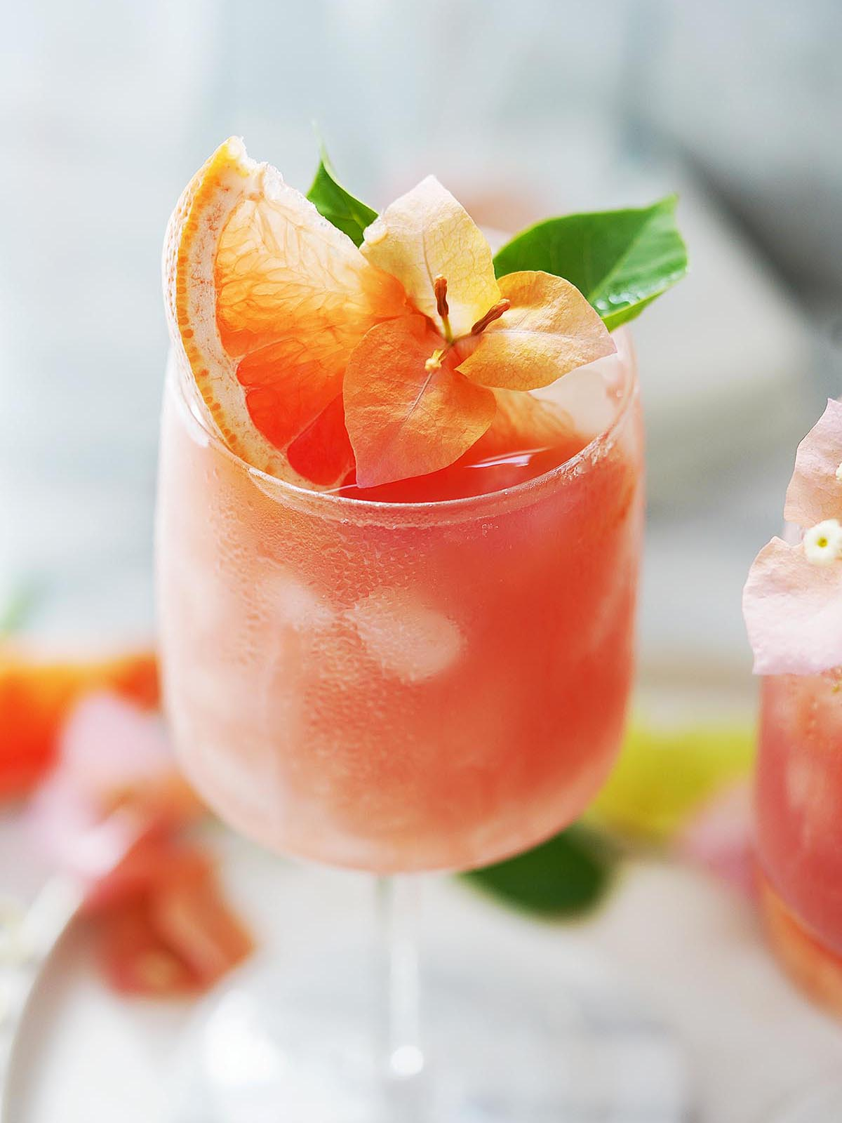 A Paloma cocktail garnished with grapefruit and an orange flower.
