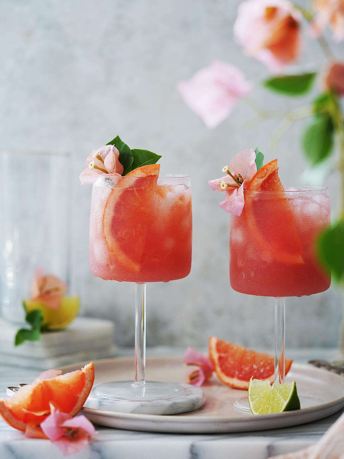 two glasses filled with an orange drink and garnished with slices of grapefruit.