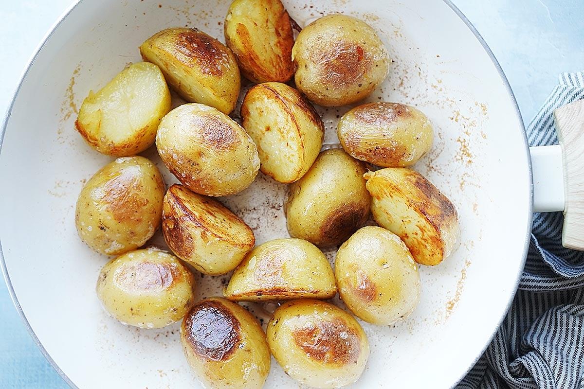 White small potatoes gettin crispy inside a white skillet.