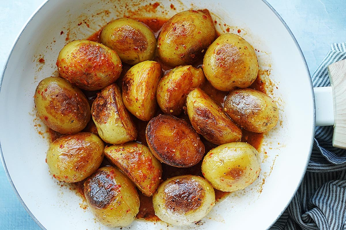 Spicy Potatoes in a white pan.