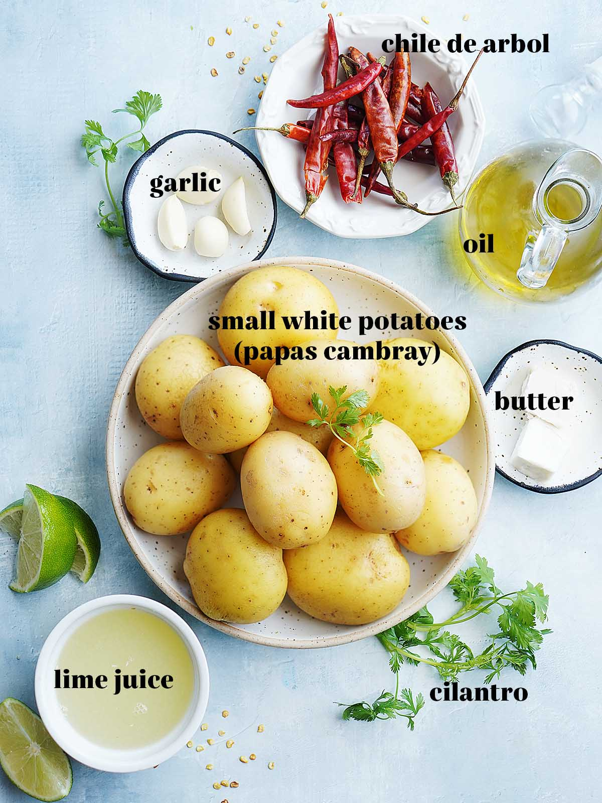 Ingredients on bowls: small yellow potatoes, lime juice, butter, cilantro, oil, garlic, chile de arbol peppers.