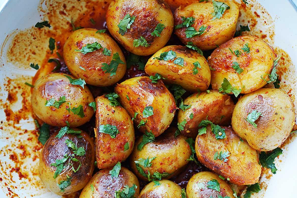 Small white potatoes inside a white skillet.