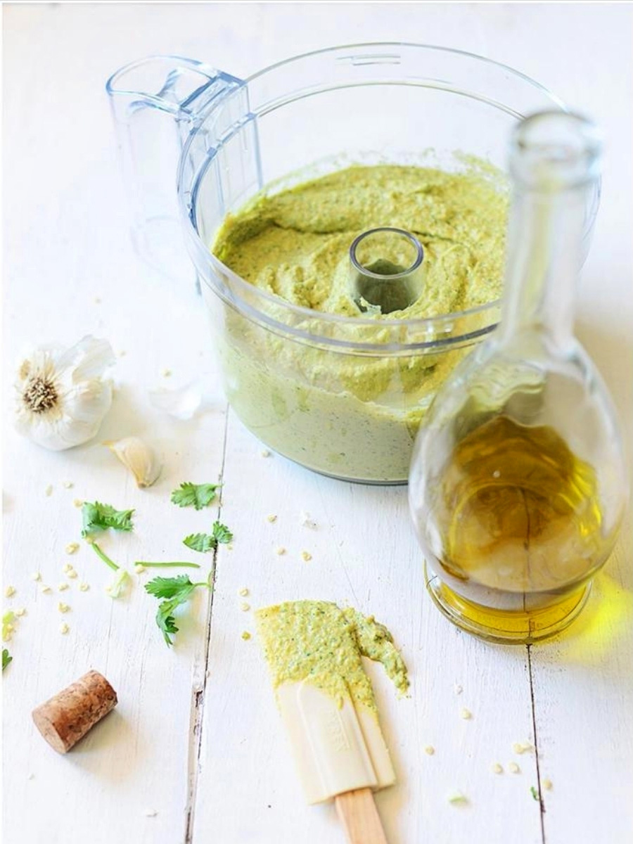 A food processor bowl with green hummus and a bottle of oil on the side.