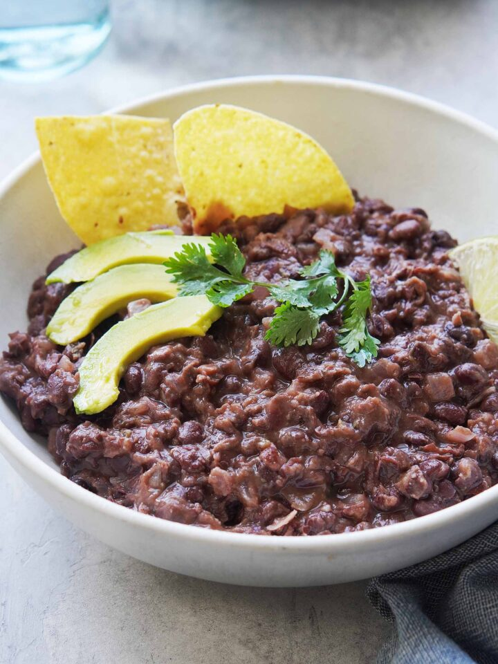 A bowl of black beans with chips on the side