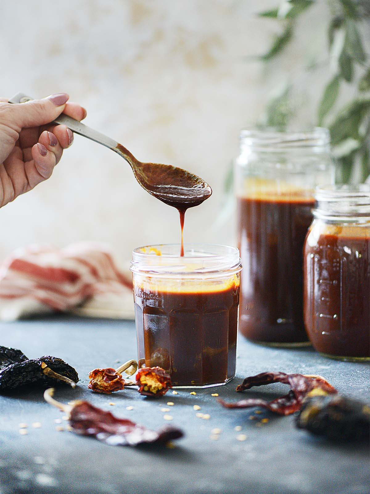 3 jars with red salsa and a spoon.