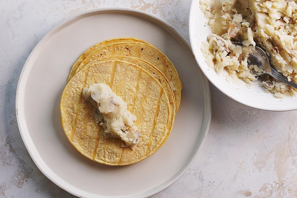 A stack of tortillas with a little bit of potato mix on one tortilla.