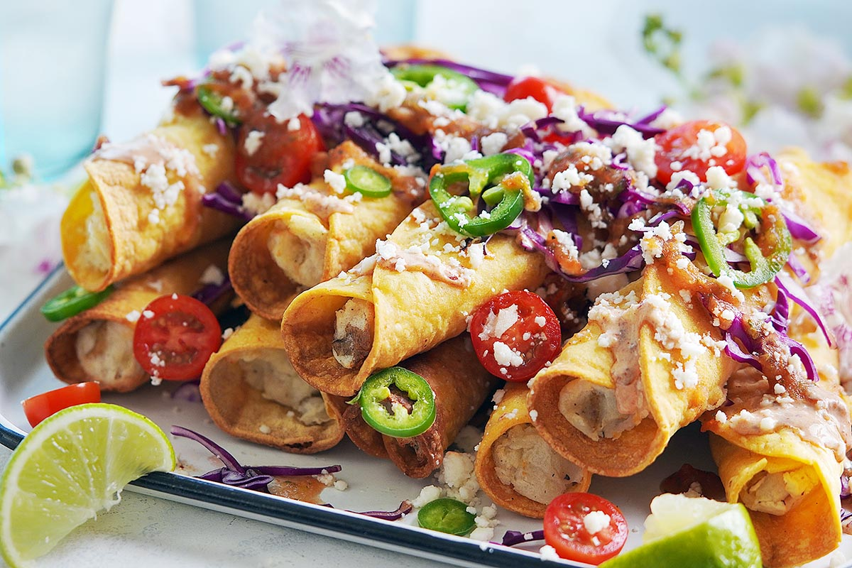 A tray with rolled taquitos and garnished with veggies.