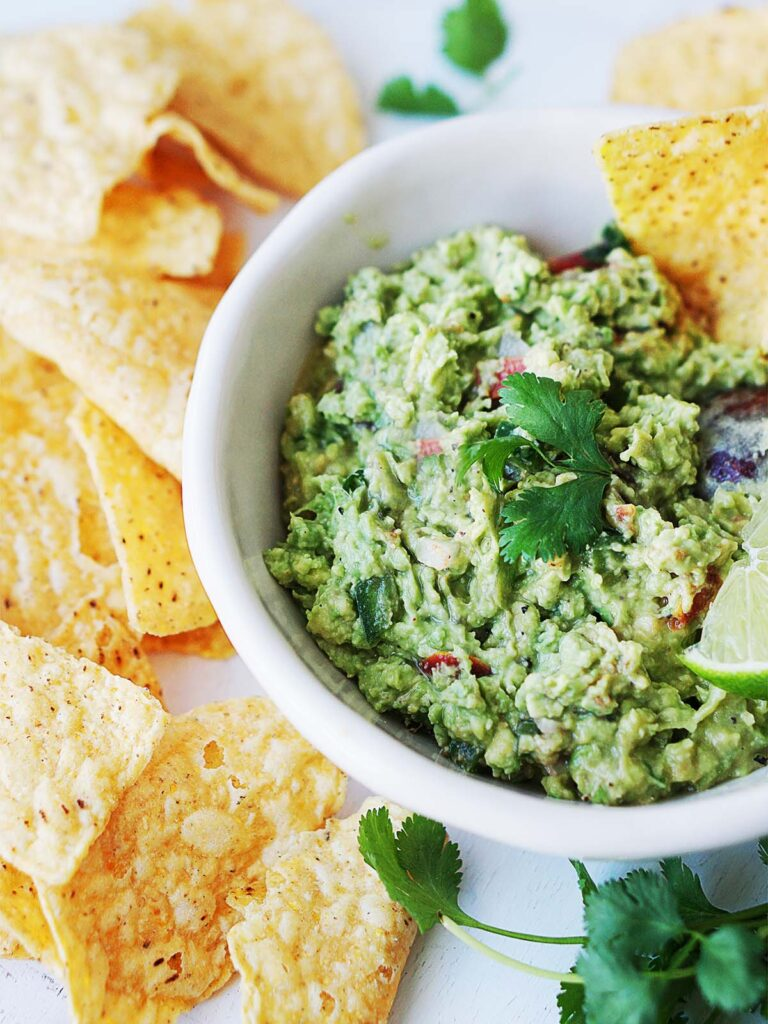 a bowl of guacamole with tortilla chips on the side.