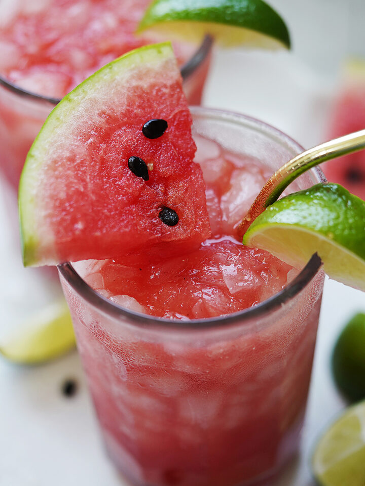 A tall glass with watermelon drink topped with a watermelon slice.