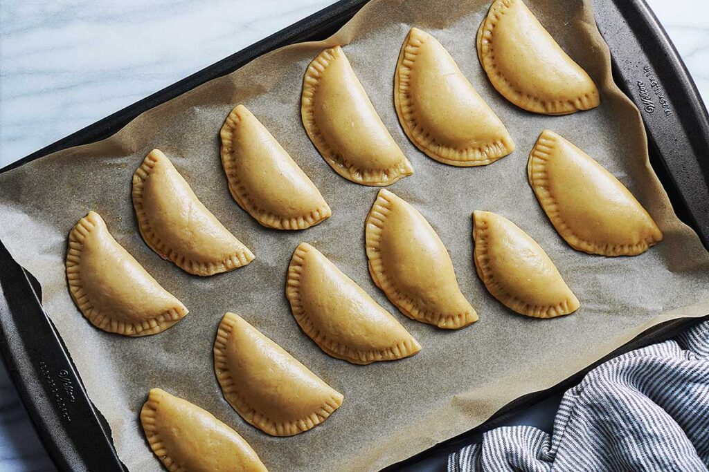 A baking tray lined with empanadas ready to bake.