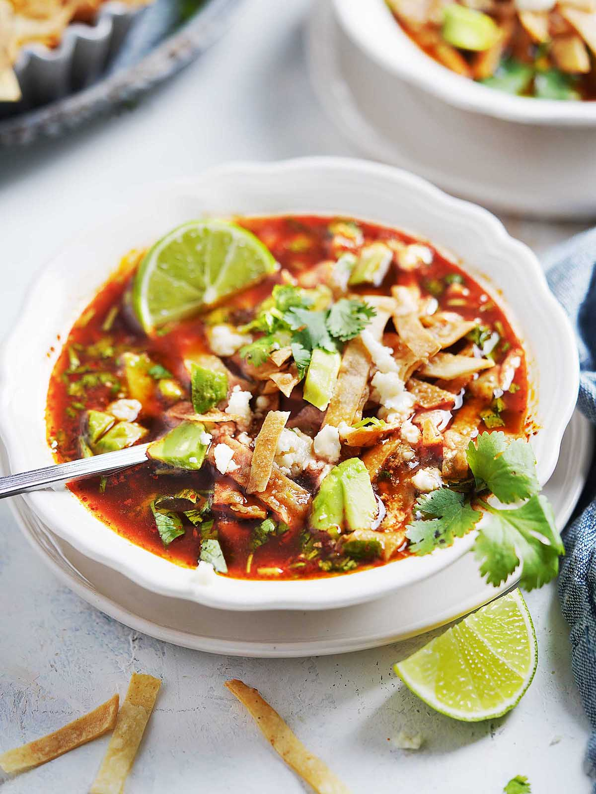 White bowl with tortilla soup garnished with avocado and cilantro.