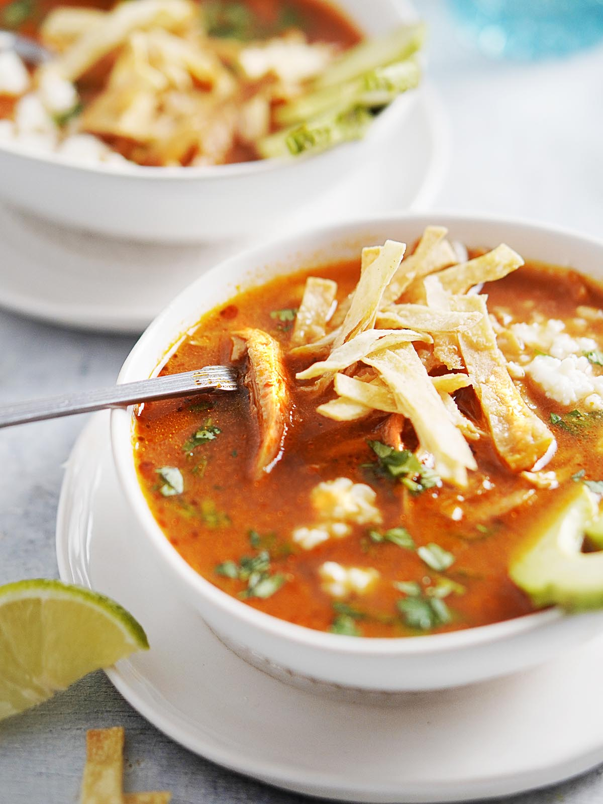 Two white bowls with sopa de tortilla and a spoon. Limes on the side.