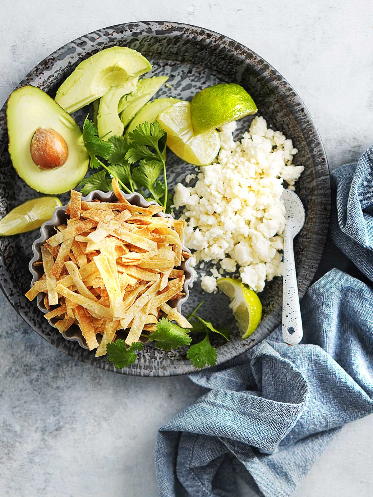 A metal plate with tortilla strips, crumbled cheese, sliced limes and avocado.
