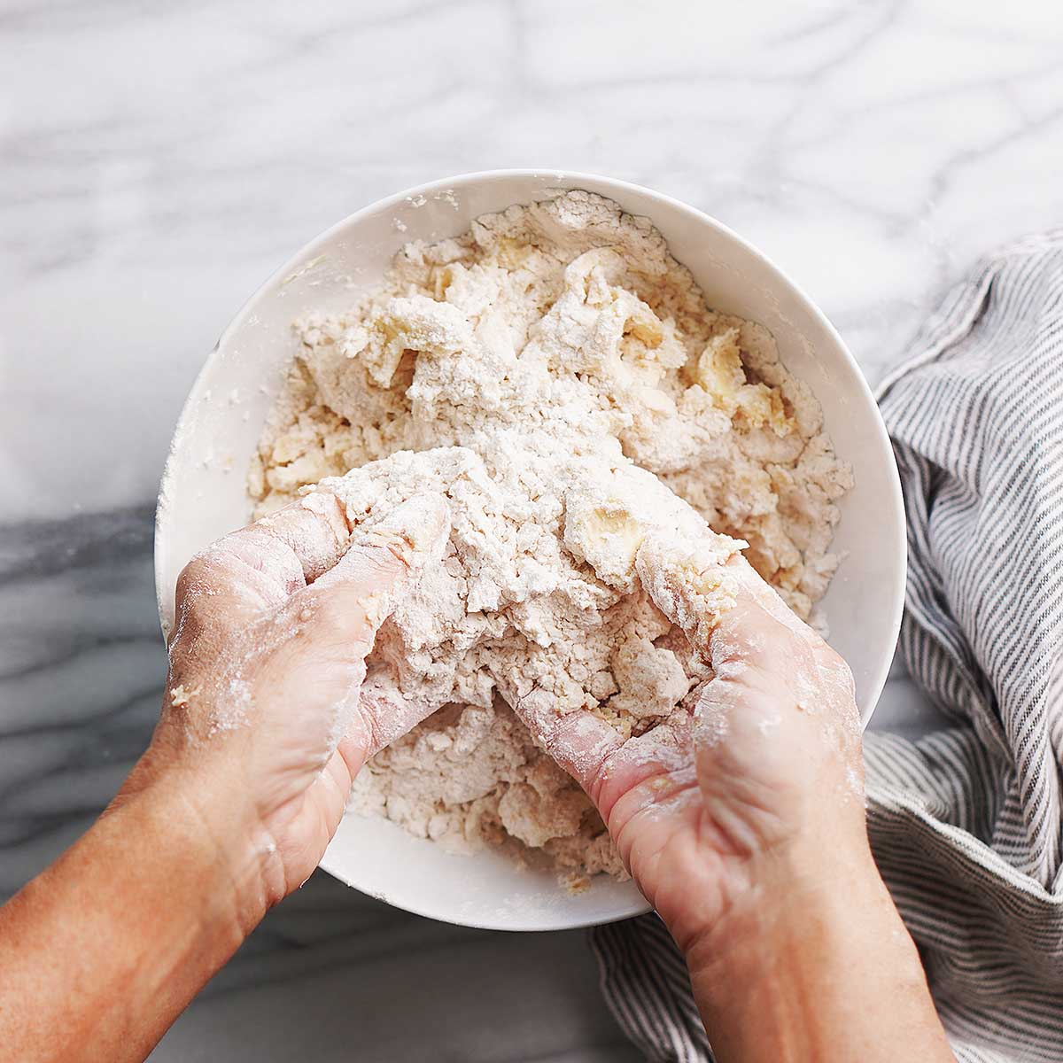 Mixing flour and butter in a large white bowl.